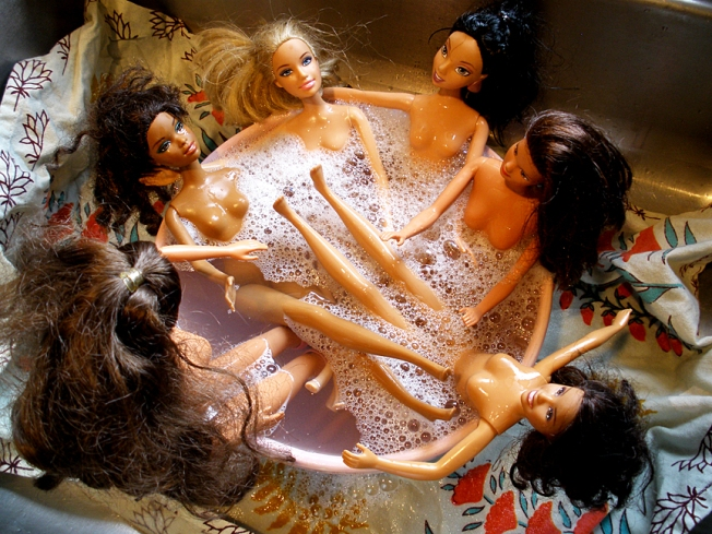 Some Barbies soaking in a bubble bath